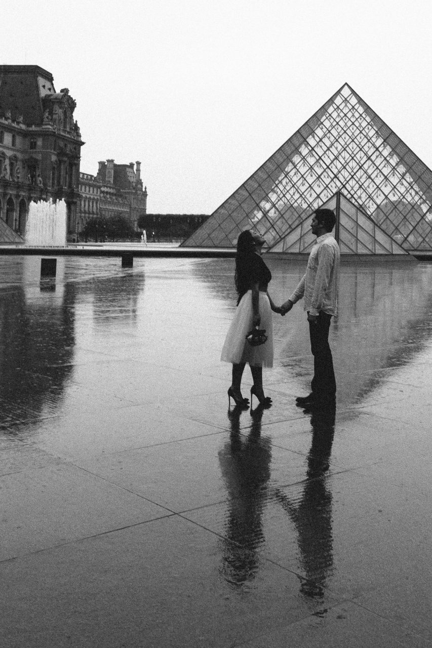 Couple black and white in the rain Pyramid Louvre Paris