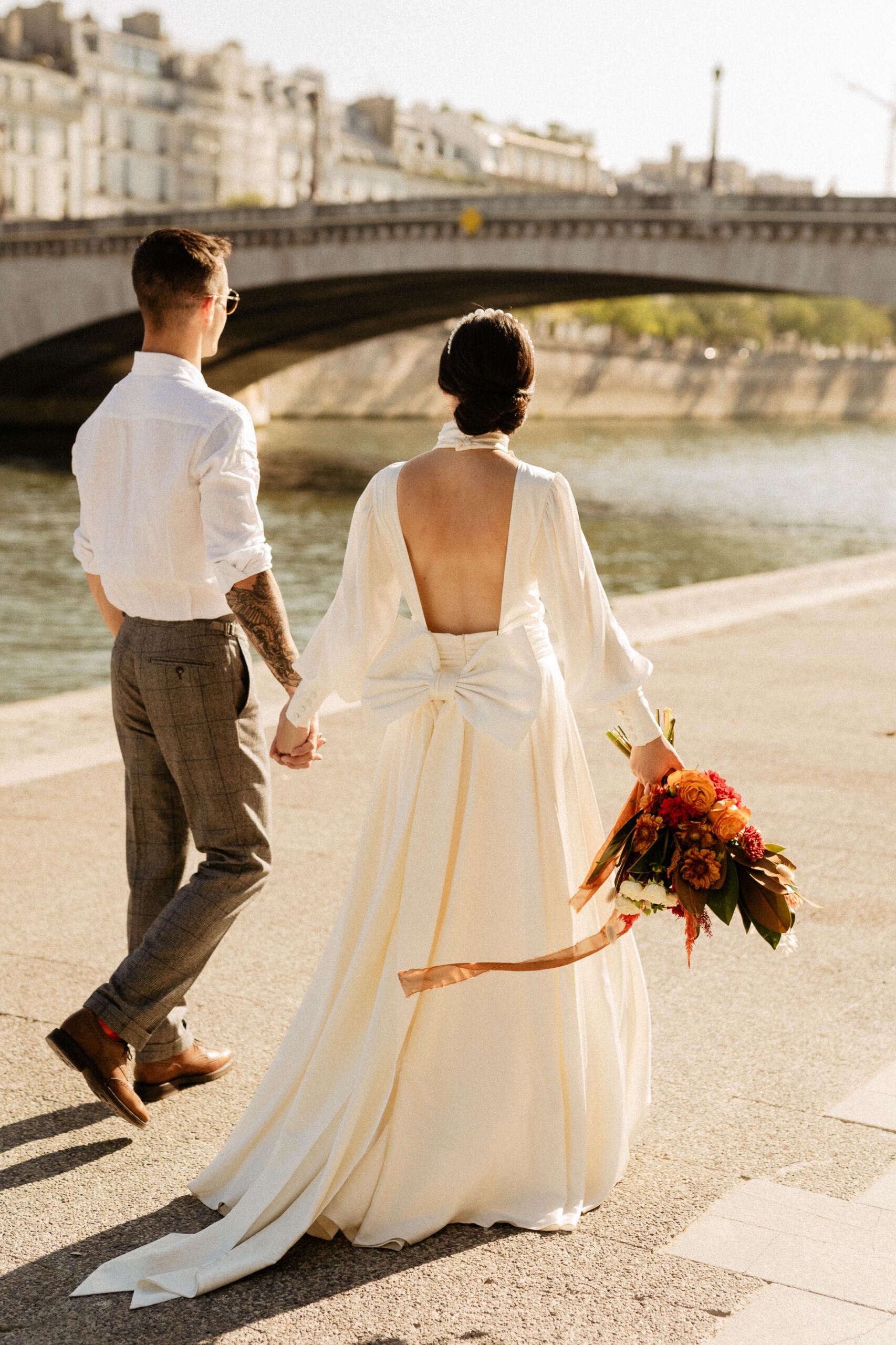 Bride and groom walking by the Seine paris wedding